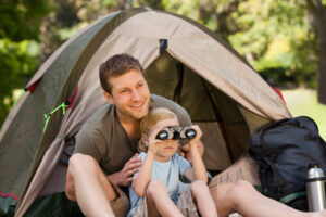 dad and daughter outside of tent with binoculars